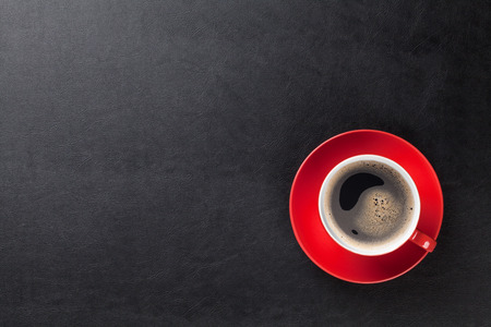 taza de café: Mesa escritorio de cuero de la oficina con la taza de café. Vista superior con espacio de copia