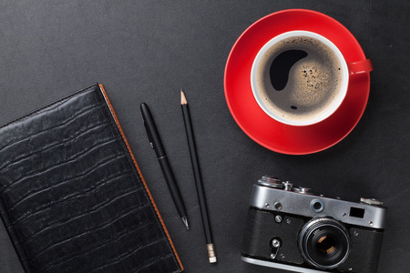 page views: Office leather desk table with camera, supplies and coffee cup. Top view