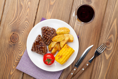 grilled potato: Steak with grilled potato, corn and red wine on wooden table