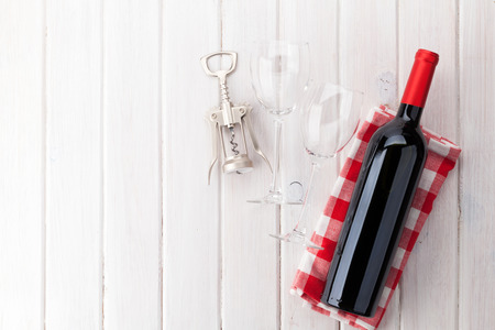 Red wine bottle, glasses and corkscrew on white wooden table background with copy space Stock Photo