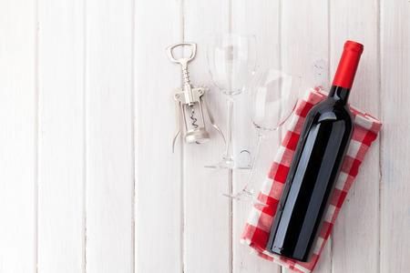 Rode wijnfles, glazen en kurketrekker op witte houten lijstachtergrond met exemplaarruimte