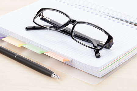 phonebook: Office table with glasses over blank notepad