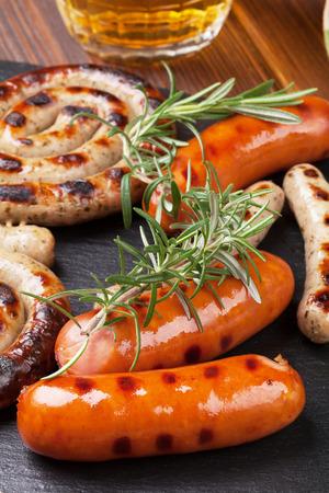 saucisse: Saucisses grillées et chope de bière sur la table en bois