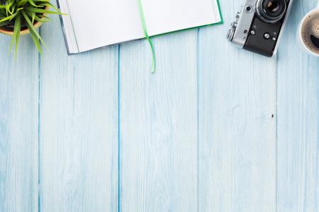 メモ帳、カメラ、コーヒー、花オフィス デスク テーブル。コピー スペース平面図