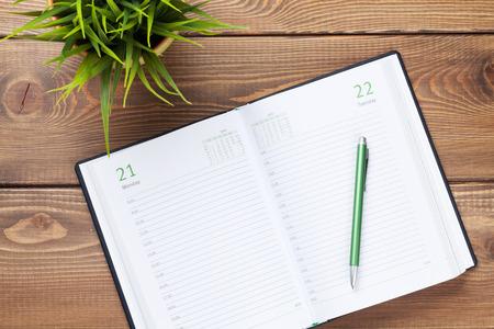 articulos oficina: Bloc de notas de calendario y flores sobre la mesa de madera. Vista superior