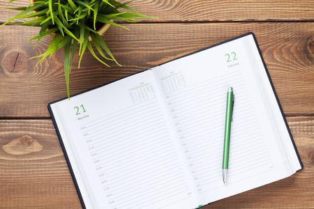 kalendarium: Kalendarz notatnik i kwiaty na drewnianym stole. Widok z góry Zdjęcie Seryjne