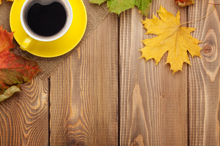 autumn grunge: Autumn leaves and coffee cup over wood background with copy space