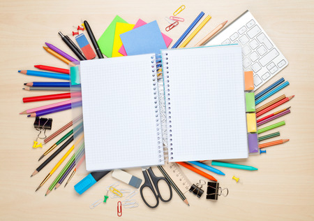 office space: Blank notepad over school and office supplies on office table. Top view with copy space