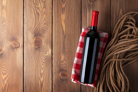 vino: Red wine bottle over rustic wooden table background with copy space Stock Photo