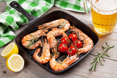 tiger shrimp: Grilled shrimps on frying pan and beer on wooden table