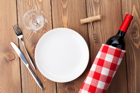 fork glasses: Table setting with empty plate, wine glass and red wine bottle. Top view over rustic wooden table background