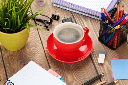 tazas de cafe: Office table with flower, supplies and coffee cup. View from above