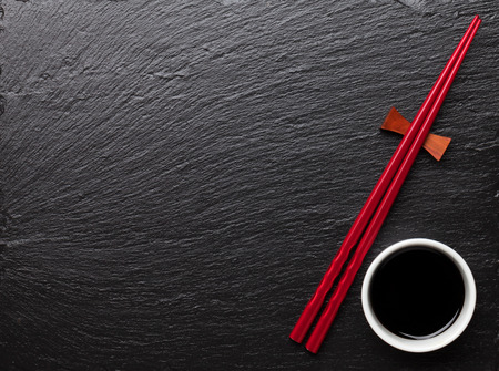 Japanese sushi chopsticks and soy sauce bowl on black stone background. Top view with copy space Imagens - 43447617
