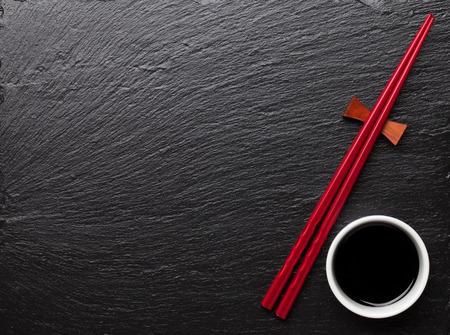 Palillos de sushi japonés y un tazón de salsa de soja sobre fondo negro de piedra. Vista superior con espacio de copia Foto de archivo - 43447617