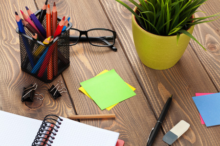 office space: Office table with flower, blank notepad and supplies. View from above with copy space Stock Photo