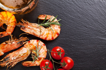 Beer mug and grilled shrimps on stone plate. Top view with copy space Foto de archivo