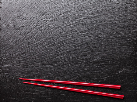 black stone: Japanese sushi chopsticks on black stone background. Top view with copy space