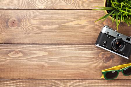 trompo de madera: C�mara fotogr�fica, lentes de sol y la flor en la oficina de mesa de escritorio de madera. Vista superior con espacio de copia Foto de archivo