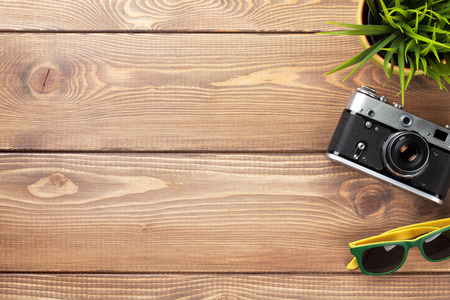 wood work: Camera, sunglasses and flower on office wooden desk table. Top view with copy space