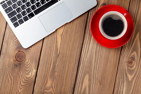 オフィス デスク テーブル ラップトップ コンピューターとコーヒー カップ。コピー スペース平面図