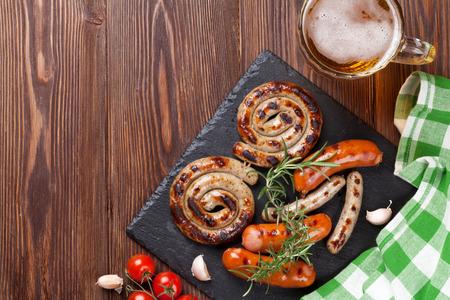 trompo de madera: salchichas a la parrilla y jarra de cerveza en la mesa de madera. Vista superior con espacio de copia Foto de archivo