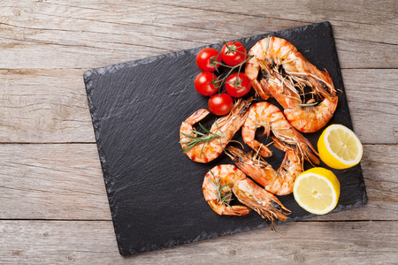 Grilled shrimps on stone plate over wooden table. Top view with copy space Banco de Imagens