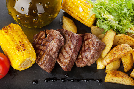 steak plate: Steak with grilled potato, corn, salad and tomato on stone plate Stock Photo