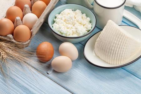 木製テーブルの上の乳製品。サワー クリーム、牛乳、チーズ、卵、ヨーグルト