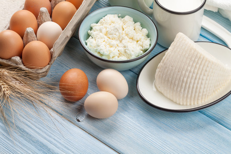 eggs: Dairy products on wooden table. Sour cream, milk, cheese, eggs and yogurt Stock Photo