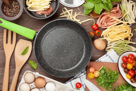 Pasta koken ingrediënten en gebruiksvoorwerpen op houten tafel. Bovenaanzicht met een kopie ruimte Stockfoto