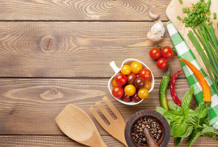 cooking oil: Cooking ingredients on wooden table. Spring onion, basil, tomato, olive oil.