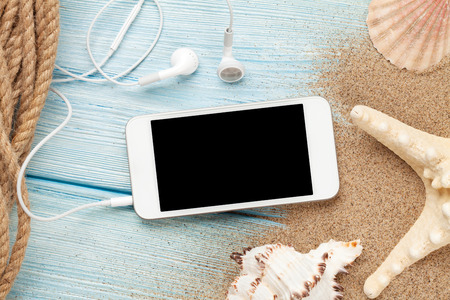 view on sea: Smartphone on wood and sea sand with starfish and shells. Top view with copy space
