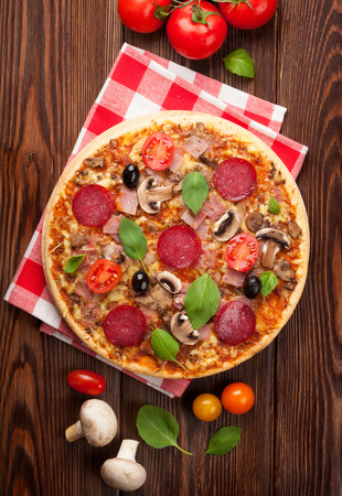 above: Italian pizza with pepperoni, tomatoes, olives and basil on wooden table. Top view
