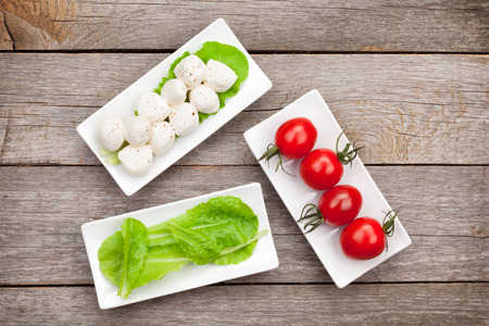 mozzarella cheese: Tomatoes, mozzarella and green salad leaves on wooden table background Stock Photo
