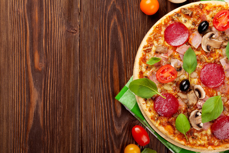 ingredients: Italian pizza with pepperoni, tomatoes, olives and basil on wooden table. Top view with copy space