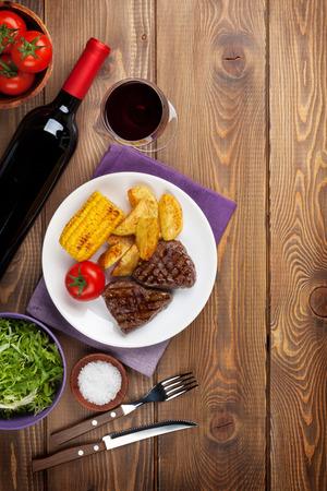 ensalada de verduras: Filete a la plancha con patatas, ma�z, ensalada y vino tinto en la mesa de madera. Vista superior con espacio de copia Foto de archivo