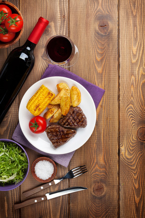 grilled vegetables: Steak with grilled potato, corn, salad and red wine on wooden table. Top view with copy space