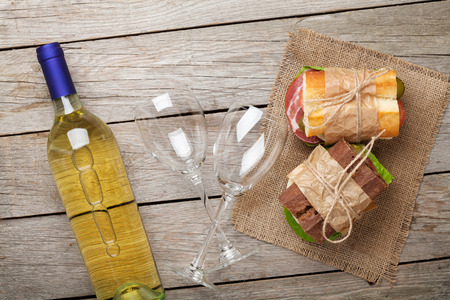 wine glass: Two sandwiches and white wine on wooden table. Top view