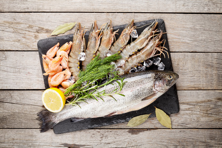 sea view: Fresh raw sea food with spices on stone plate over wooden table background. Top view