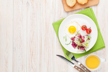english breakfast: Healthy breakfast with fried egg, toasts and salad on white wooden table. Top view with copy space