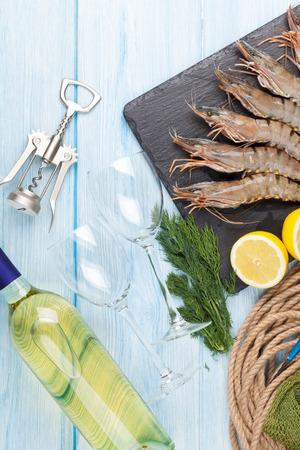 plato de pescado: gambas frescas crudas tigre, especias y vino blanco sobre la mesa de madera
