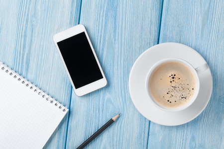 Coffee cup, smartphone and blank notepad on wooden table background. Top view with copy space