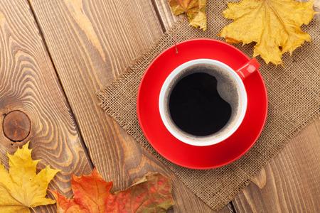 planta de cafe: Hojas de otoño y la taza de café sobre fondo de madera con espacio de copia