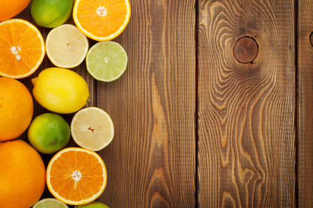 citrus fruits: Citrus fruits. Oranges, limes and lemons. Over wooden table background with copy space