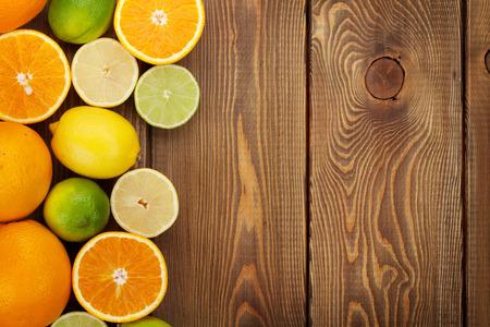CITRICOS: Frutas cítricas. Naranjas, limas y limones. Con el fondo de la tabla de madera con espacio de copia
