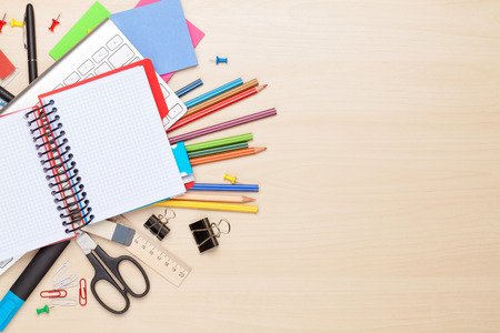 Blank notepad over school and office supplies on office table. Top view with copy space