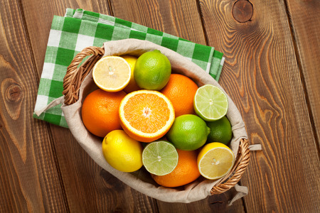 Citrus fruits in basket. Oranges, limes and lemons. Over wooden table background