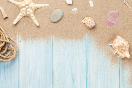 Sea sand with starfish and shells on wooden table. Top view with copy space