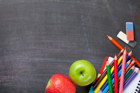 School supplies and apples on blackboard background. Top view with copy space