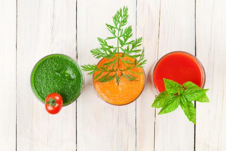 tomate: Frais smoothies de légumes sur la table en bois. Tomate, concombre, carotte. Vue de dessus
